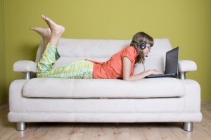 A young lady is enjoying her Skype interview, lying on a sofa while talking to the employer. She wears no socks