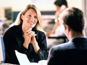 Interview led informally in a cafeteria. The job candidate feels good about her chances, she is smiling.
