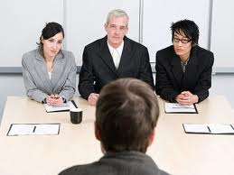 Three executives interview a job applicant for a senior position. We can see two men and one woman in the interviewing panel.