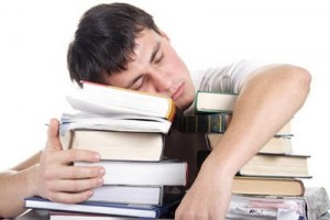 A man is sleeping on a pile of books. He has overdone it with his interview preparation.