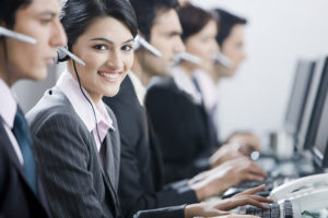 Line of assistants in a big company. All of them wear heaphones with microphones, and type something on the keyboards.