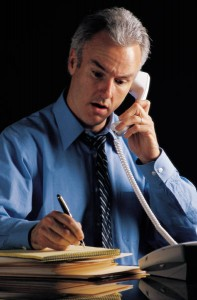 Man is making notes during his phone interview, whe wears blue shirt and black tie