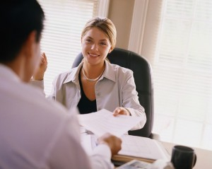 A job candidate is handing her resume to the interviewer. They look each other in the eyes, and the atmosphere is relaxed.
