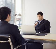 An HR director tests the job applicant with the question about their weaknesses. Now he is quiet, holding his pen close to his mouth, waiting for the applicant's reaction.