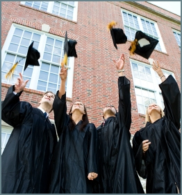 College students celebrating their graduation, with a tradition of throwing their graduation caps to the air. We can see four students, two men and two woman, doing it in front of a school building.
