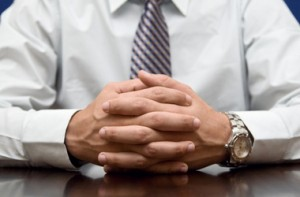 Job applicant nervously sitting in an interview, with his fingers crossed together. We can see his white shirt and blue tie
