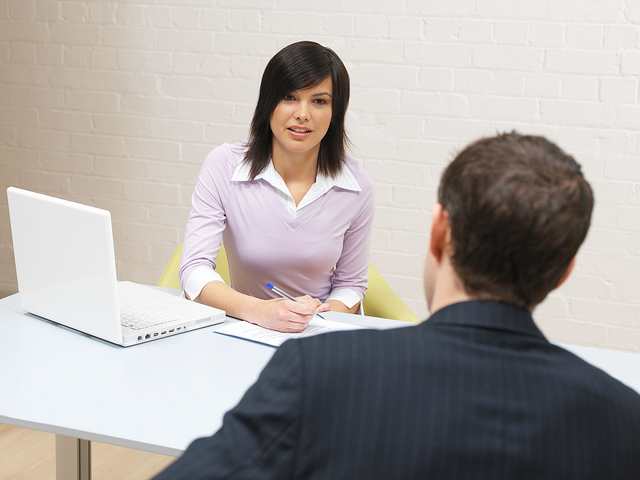 In person interview for a position of a counselor. An assistant principal, a good looking woman in her thirties, interviews a man who tries to get a job. We can see a white laptop on the table that stands between the two.