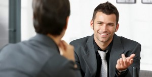 Man interviews for a job with an HR generalist. Both men wear the same clothes, and they are smiling.