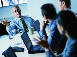 People in a group interview, an HR manager assigns a tasks from them. We can see three job candidates with computers on the picture.