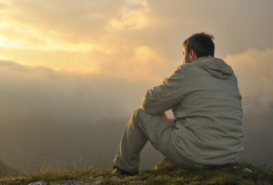 man is sitting on the top of the hill, looking at the sky, thinking about his life