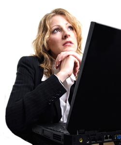 A woman in business attire sits in front of her computer, looking nervous. She struggles with her preparation for personal interview questions.