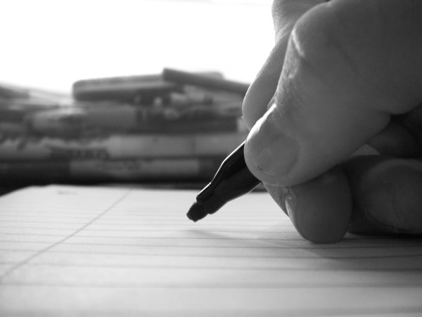 A man is writing a job application. The picture shows a black pen in hand and a paper job application.