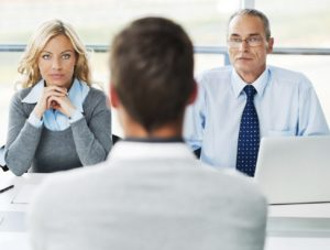 A picture taken in a job interview. A young man interviews in front of two hiring managers.