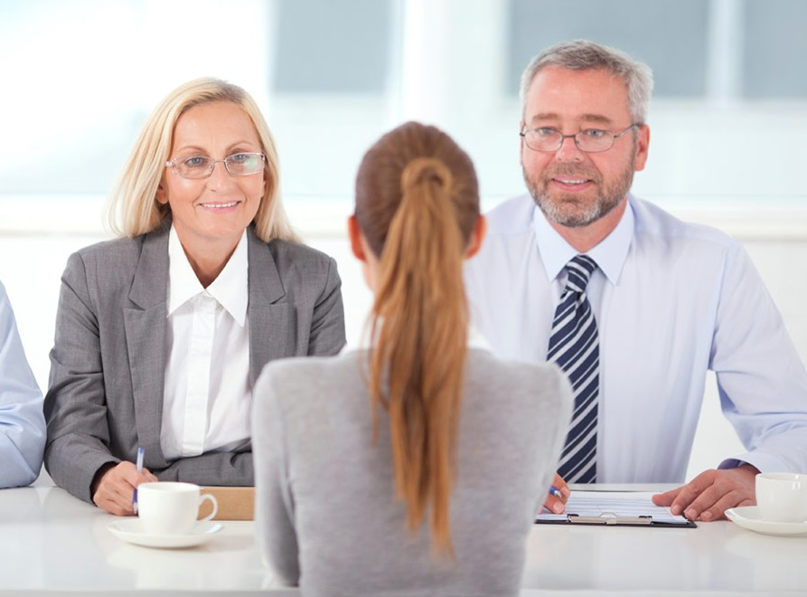 Job interview in an international corporation. An older manager and his colleague sit on one side of the table, and a young woman, a job candidate sits on the another one.