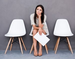 Young woman is sitting on a white chair, holding some papers in her right hand. She waits for an interview.