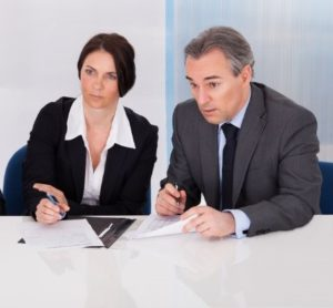 Two recruiters listen attentively and make notes. We can not see the job applicant on the piture.