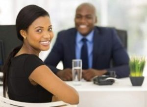 An illustation of a job interview, a woman and man smile and talk together. They are formally dressed, both in black.