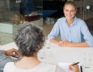 A young woman interviews for a job. We can see two interviewers in the background of the picture.