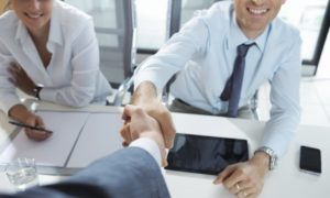 People shake hands in a job interview. We can see two man shaking hand, smiling. One sits at the table and the another one is standing.