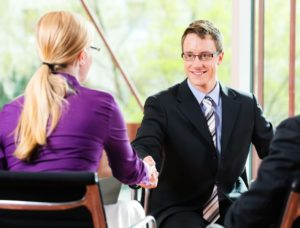 Handshake at the end of a successful job interview. Man in a black suit shakes hands with a woman in a nice pink shirt.