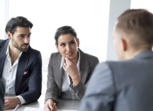 Two young hiring managers listen to the job applicant, while he answers one of their behavioral questions.