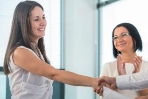 Two women in white shirts shake their hands, while the third one applauds. The picture illustrates a positive outcome of a job interview.