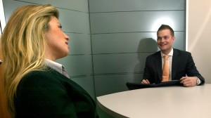 An interviewer ask a job candidate some behavioral questions. She looks rather tired, but he is in a good mood. We can see a big table in the room, and both persons sit at the table.