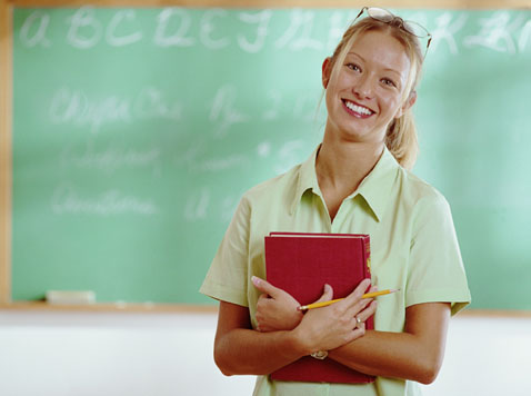 A happy teacher stands in front of a blackboard. She hold a pencil and a big red book, likely the Bible, in her hands.