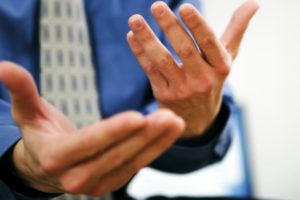 A man is gesticulating with his hands, trying to explain a difficult issue to someone else. We can not see the recipient of his message on the picture.