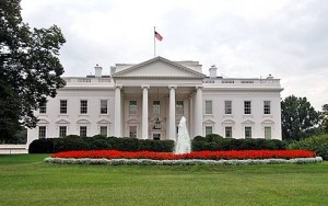 One of the government buildings in the United States. We can see bed of flowers and green grass in front of the building.