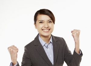 A woman is happy, because she did well in her group interview. Her smile and gestures indicate her happiness.