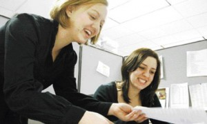 Two girls are having a good time, checking their job applications before the start of the interview.