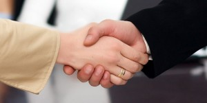 Handshake of two people, man and woman. Woman has a ring on one of her fingers