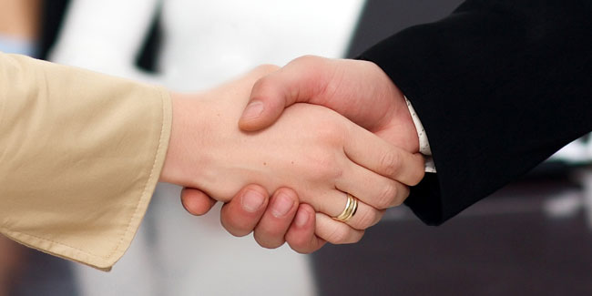 Shaking hands in the final interview, we can see two hands, man wears a black jacket, a woman a brown one.
