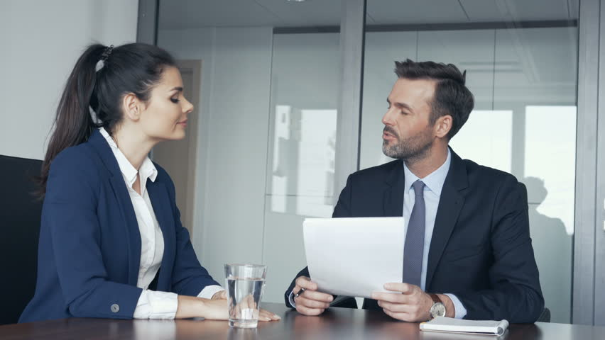 Illustration of a job interview. We can see a man and a woman on the picture, talking in a nice office. The man holds some papers in his hands, and the woman has a glass of water.