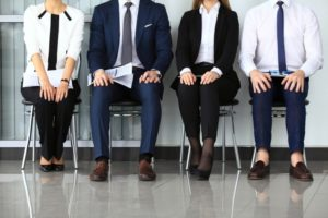 Four job applicants are nervously waiting for an interview. We can not see their heads, just their bodies, but their body langiage betrays a lot of stress.
