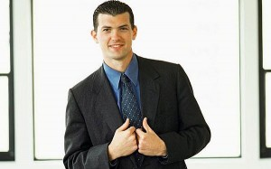 Man in a nice but simple interview outfit - black jacket, blue shirt, blue tie, and positive body language.