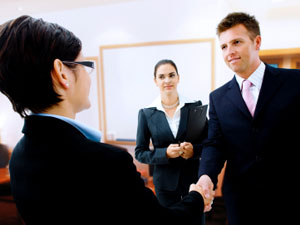 Man tries to make a good first impression in an interview, with a firm handshake and a smile. the interviewer (woman with short hair and glasses) doesn't look very impressed though.