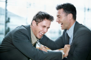 two businessmen are having a good laugh, holding each other. The picture illustrates a funny situation from an interview.