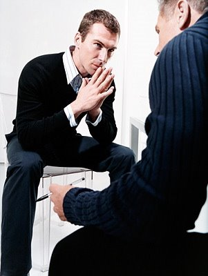 A picture of an interview coach working with the client. They mock an interview, and the client answers some interview questions.
