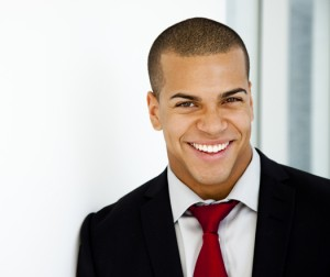 A man witha big smile and red tie has a very positive body language. He looks very confident.