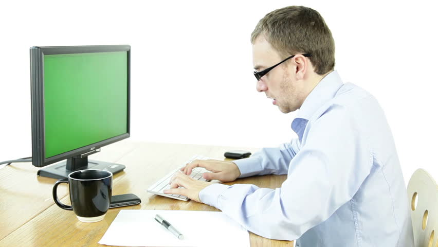 Software tester sits in front of his computer screen, performing some testing. We can see his phone and cup of coffee on the table. He wears glasses and white shirt