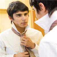 Man is making his tie in front of a mirror. He is preparing for a job interview.