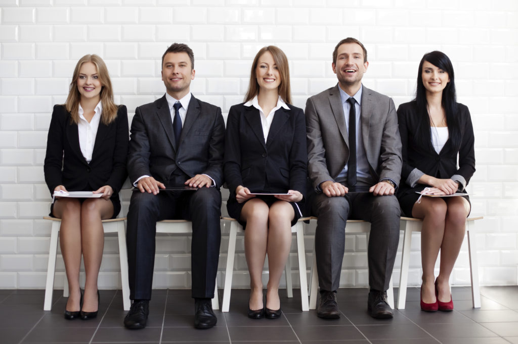 Five job applicants are waiting for their interview. Surprisingly, they seem to be in an excellent mood. Three women wear black skirts and identical tops, two men wear jackets and ties.