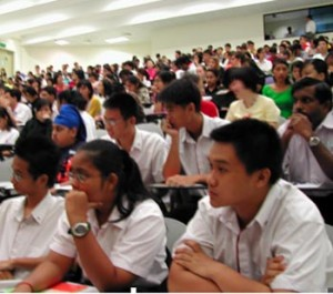 Indian students sit in a big lecture hall at the University. We can see more than a hundred students on the picture.