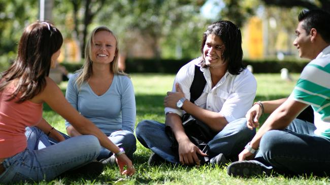 Students of University sitting in a park, three women and one man, all of them look happy and wear casual clothes