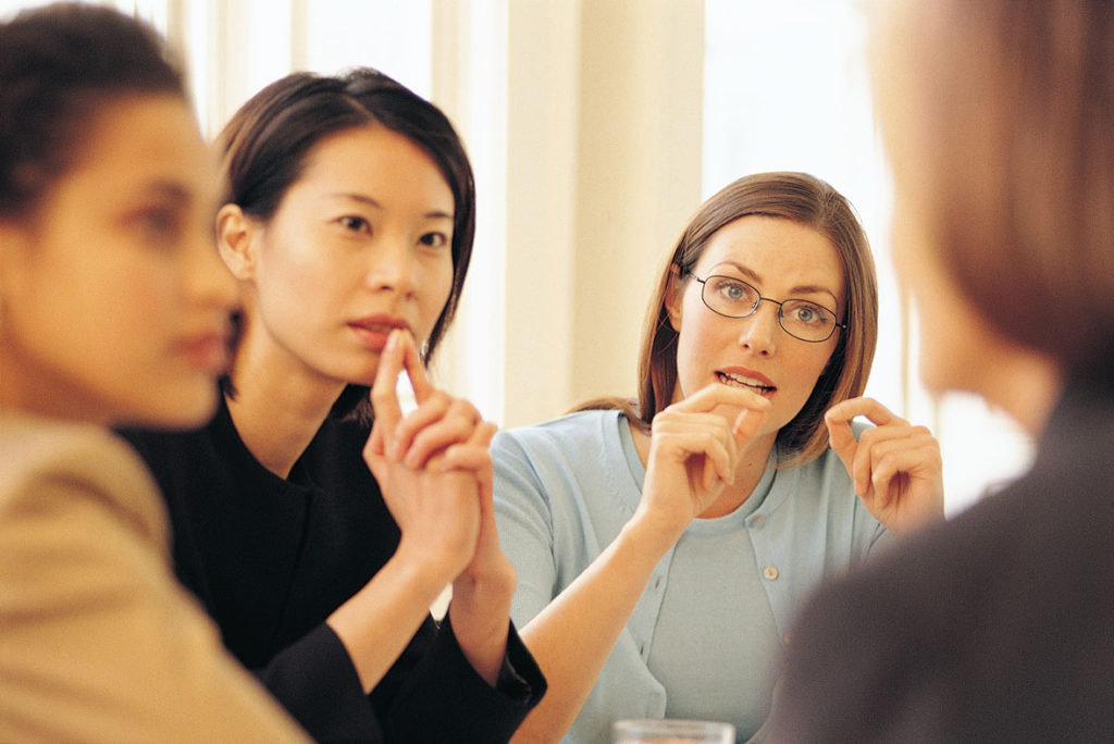 Job interview, three interviewers, all female, one of them of Asian origin, are listening to a job candidate, another woman.