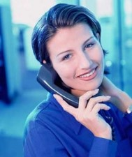 Administrative assistant job applicant is interviewing on the phone. She smiles, trying to show enthusiasm in her voice