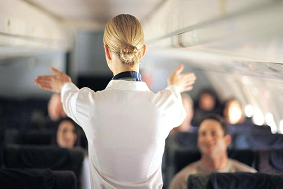 A flight attendant stands in front of the passengers and explains the safety regulations. The plane is not packed. We can see the attendent from behind.