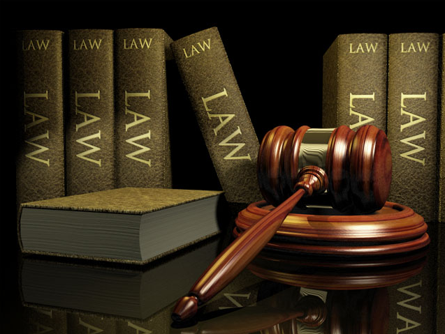 Law books and a wooden hammer on a table. Demonstration of a judicial system
